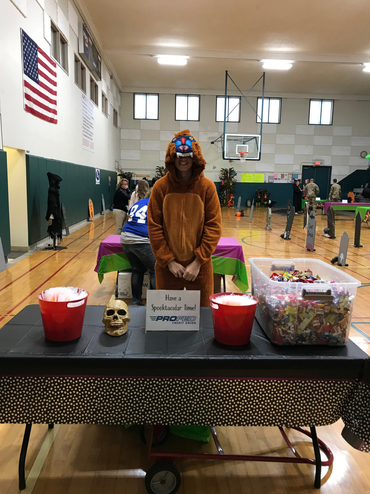 A boy in a chimpanzee costume standing behind a table passing out candy for Halloween in a gymnasium.