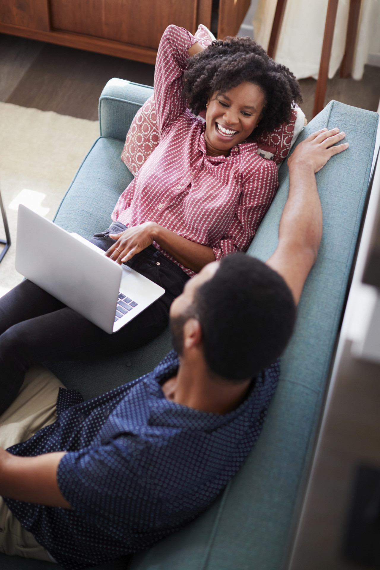 Couple sitting on sofa at home with woman using laptop computer.