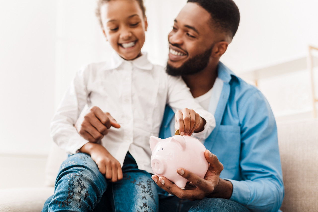A young girl with her dad placing coins in her piggy bank.