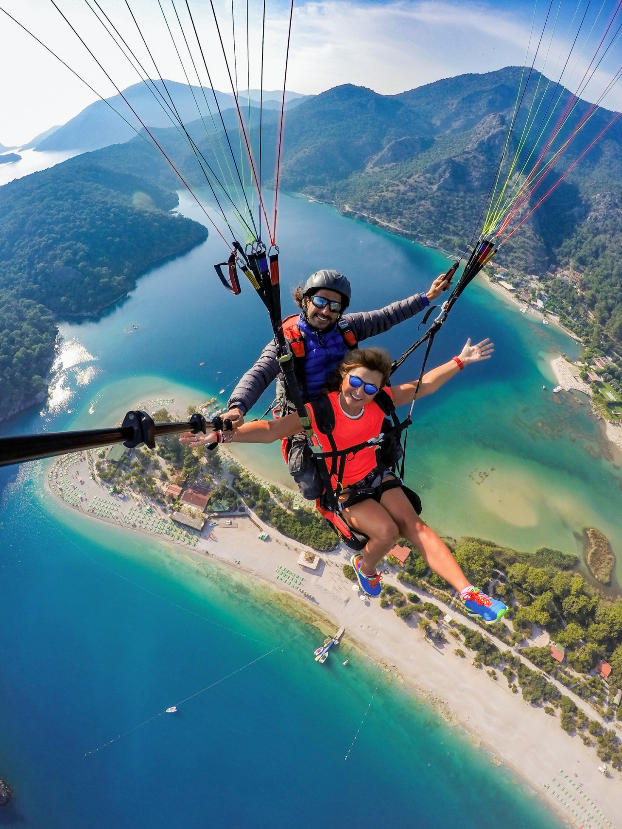 A couple tandem paragliding over an island, mountains, and blue water.