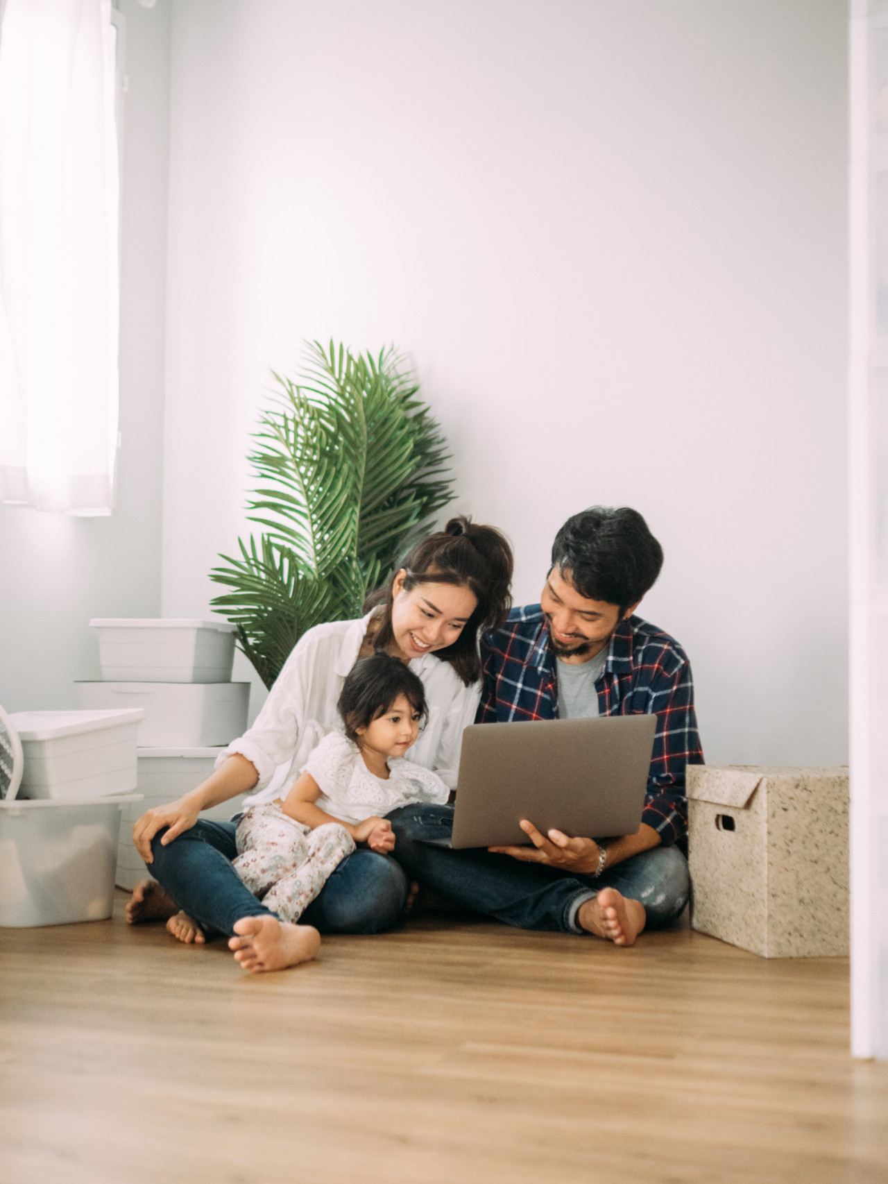 A happy family sitting on the floor in their home on their laptop.