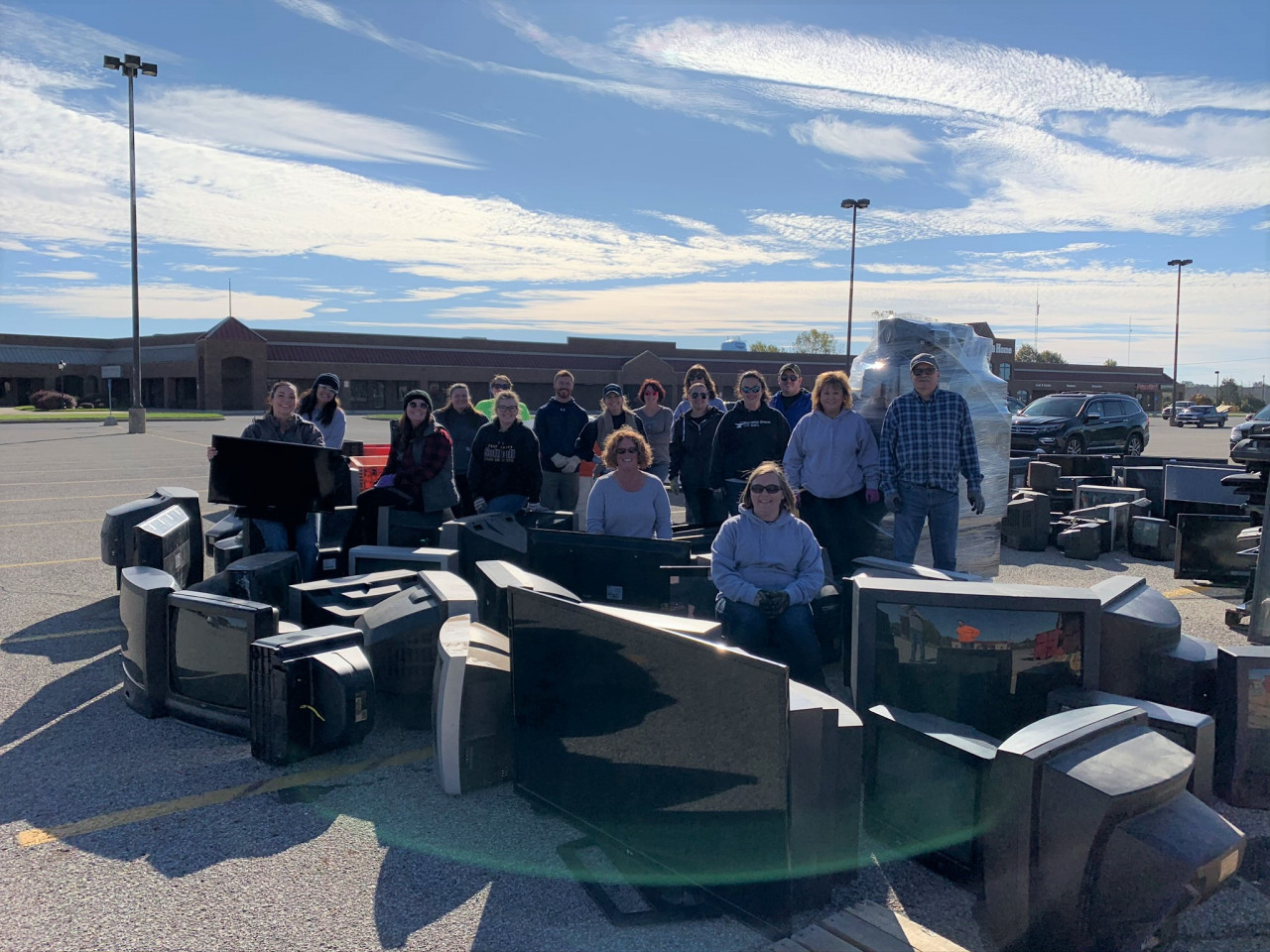 Group of ProFed employees outside the Auburn branch parking lot at eRecycling day with all the recycled electronics.